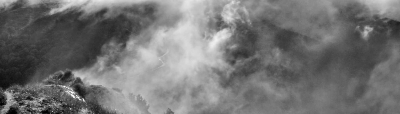 Imagen en blanco y negro de la cumbre de una montaña cubierta de nube y niebla
